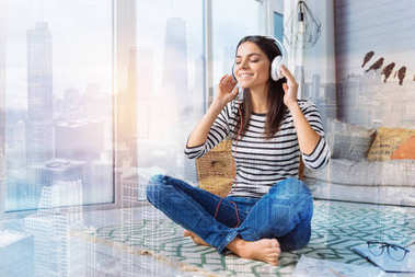 Happy woman relaxing while listening to the music at home