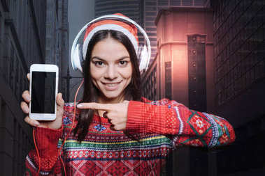 Enthusiastic positive woman pointing to the screen of her smart phone