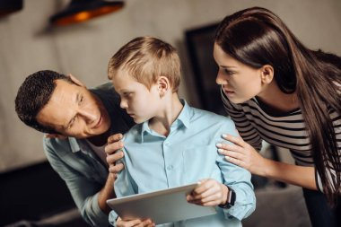 Young parents gently persuading son to put down tablet