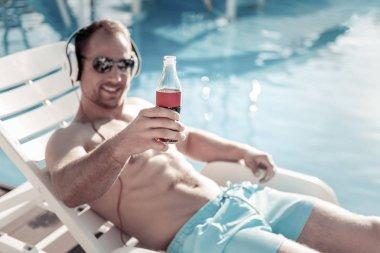 Joyful gentleman drinking sparkling water and sunbathing