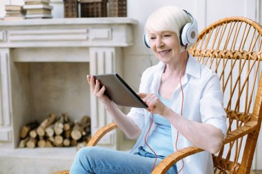 Happy pensioner sitting with a tablet