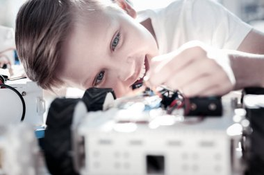 Close up of excited boy constructing robotic machine