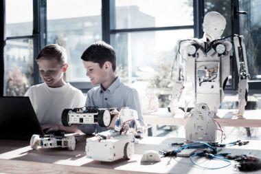 Joyful children working in workshop and programming robotic machines