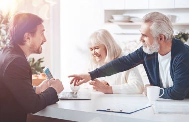 Choose the options. Cheerful professional insurance agent showign the information on laptop while meeting with elderly loving couple in the kitchen