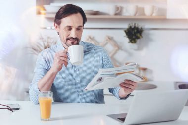 Check the news. Cheerful adult man sitting in the kitchen and reading newspaper while drinking coffee