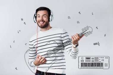 Creative musician. Cheerful talented young musician wearing big headphones and dreaming about his personal concert while playing the guitar