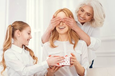 Tender daughter and grandma giving present to amazed mom