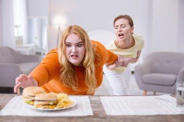 Overwhelmed fat woman reaching for a sandwich