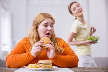 Unhappy plump woman eating a sandwich