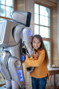 Pretty girl with long hair hugging her house robot