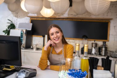 Charming young woman working as a barista in the cafe
