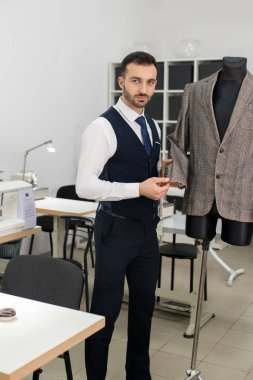 Male tailor touching and showing jacket sleeve