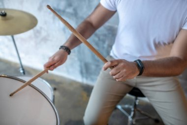 Man in a white tshirt holding drumsticks in his hands
