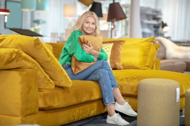 Blonde woman in a green blouse looking dreamy and positive