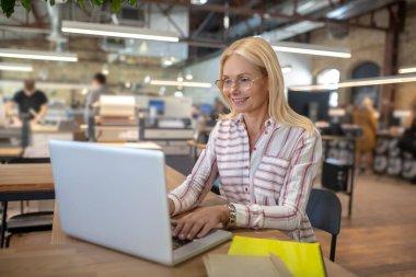 Blonde woman sitting in workshop, typing on laptop