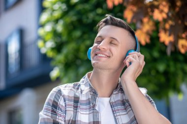 Smiling dark-haired male wearing headphones, listening to music