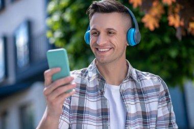 Cheerful dark-haired male wearing headphones, looking at his smartphone