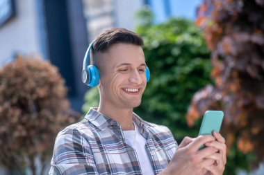 Cheerful dark-haired male wearing headphones, chatting on the phone