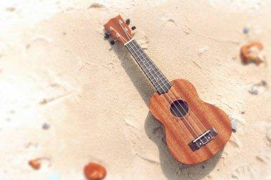 Ukulele wooden guitar on light sand close up