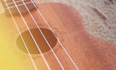 close-up photo of Ukulele wooden guitar on light sand