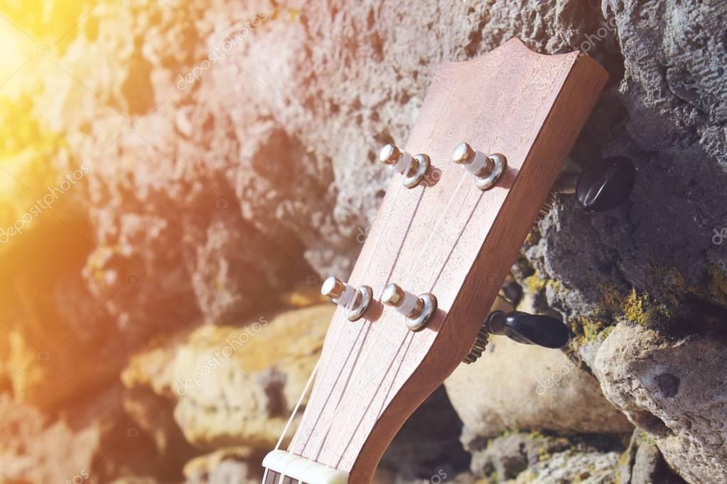 close-up photo of Ukulele wooden guitar on stoned background