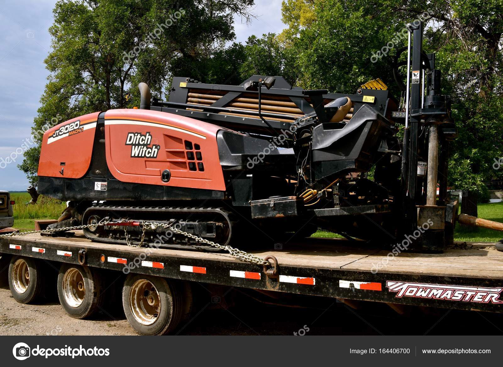 Ditch Witch trencher loaded on a flatbed trailer – Stock