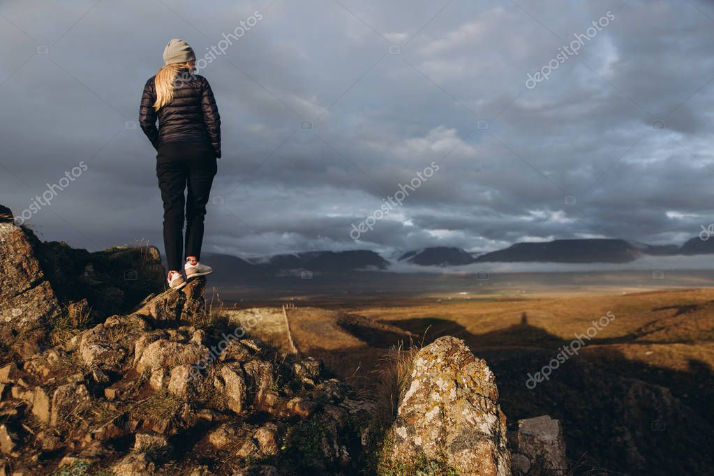 YOung woman standing on peak of the mountain
