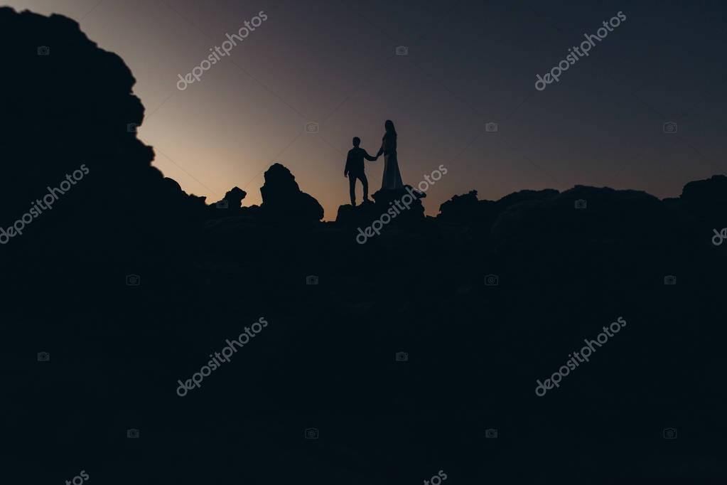 Two young lovers walking through mountains at sunset