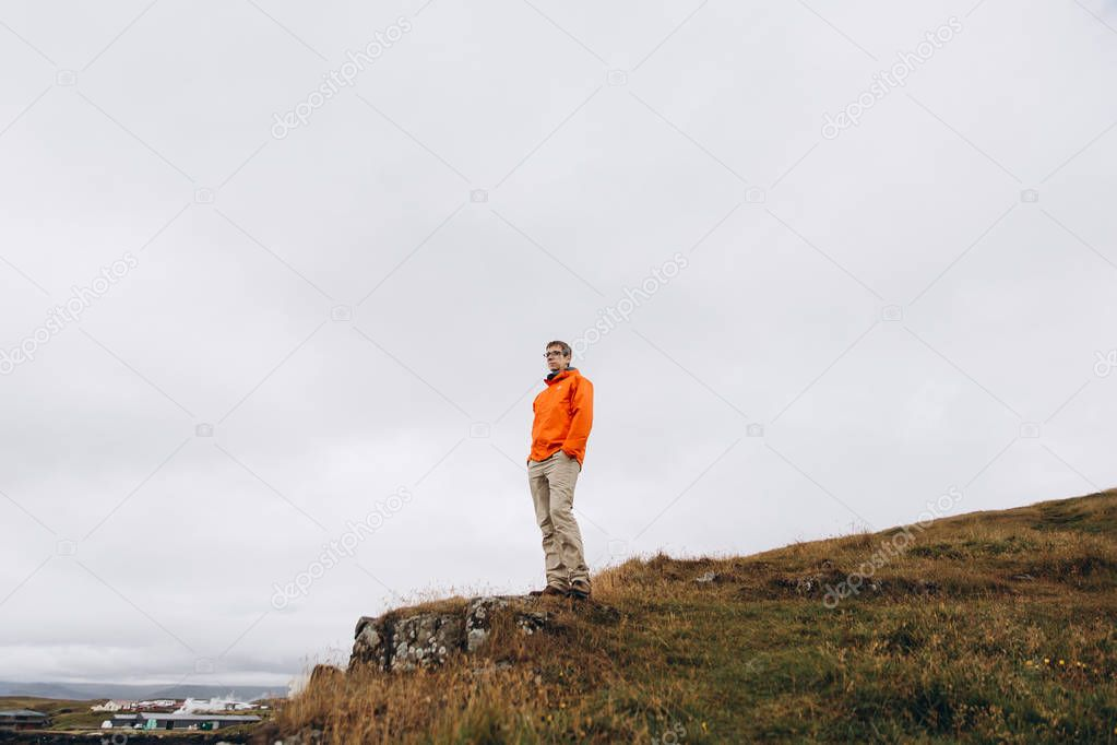 Bottom view of man standing on the edge of cliff in cold rainy day