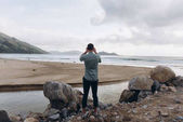 Fotografie Rear view of man standing near stones and taking photo of nature with smartphone