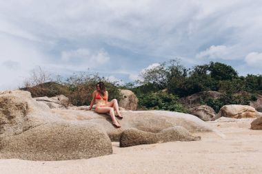 View of woman wearing red bikini sitting on boulders and posing on floral background.