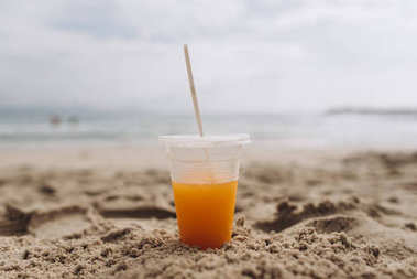 View of plastic cup with orange juice on seashore