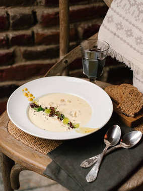 Cream soup served with two spoons on black napkin, bread slices and glass of wine on wooden chair background