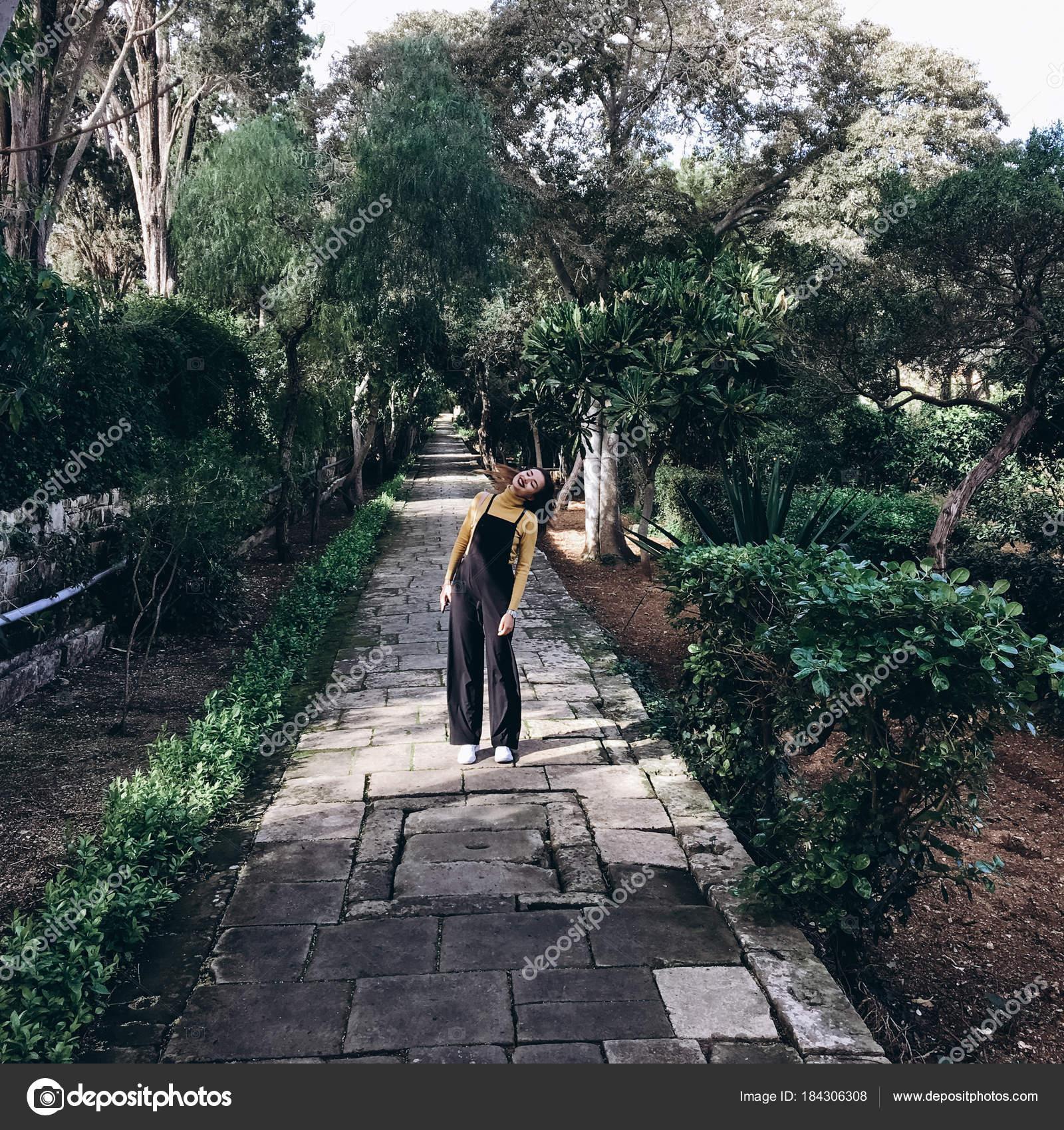 Frau Trägt Schwarze Strampler, Gelben Pullover Und Weiße Turnschuhe Zu Fuß  Auf Der Gasse Im Alten Garten U2014 Foto Von Tytbil88