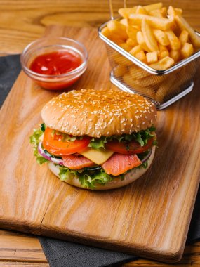 Detail view of salmon cheeseburger, french fries in basket and sweet ketchup serving on wooden cutting board and grey napkin