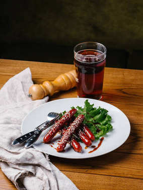 Appetizing grilled hunting sausages with sesame seeds and lettuce served on wite plate with knife, fork, dark beer glass and pepper grinder on wooden table
