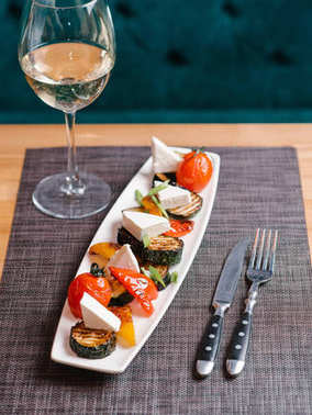 Grilled eggplants, cherry tomatoes, red and yellow peppers, green onion and feta served on long white plate with knife, fork and white wine on grey napkin