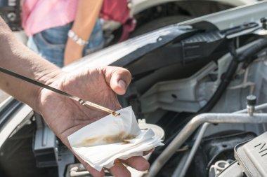 Mechanic checking motor oil
