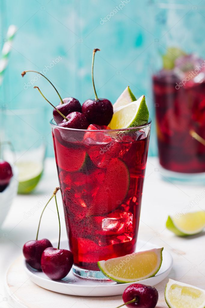 Cherry cola, limeade, lemonade, cocktail in a tall glass on a white, turquoise background
