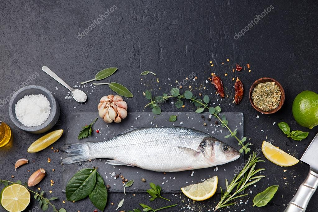 Raw fish, sea bass on slate black board Top view