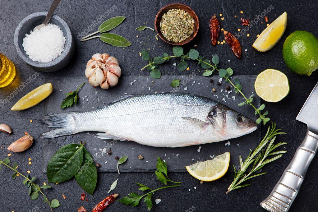Raw fish, sea bass on slate black board Top view