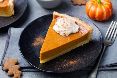 Pumpkin pie, tart with whipped cream on a plate