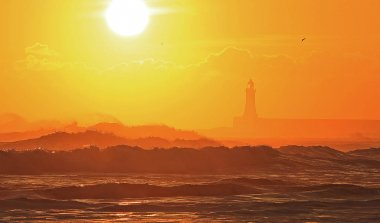 The sun rises over a rough North Sea with Tynemouth pier and Lighthouse silhouetted