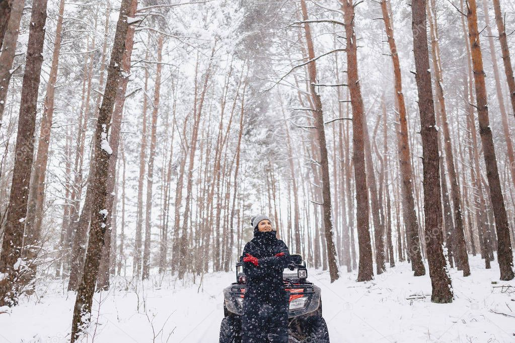 young girl on a motorcycle rides in snow-covered pine forest in