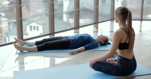 dívky cvičí jógu ve velké světlé místnosti. Trenér a student. koncepce sportovního tréninku.