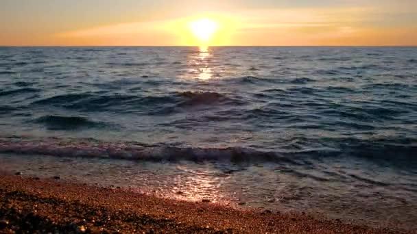 Krásný přímořský plášť při západu slunce na písečné pláži. Teplé sluneční světlo se odráží na stezce ve vodě.