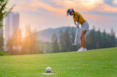 golfový míček běží téměř úspěch pokles do jamky na zelené s vzrušující sledování žen golfista v pozadí