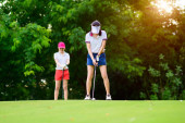 Fotografie Golfspielerin in Aktion bei der Vorbereitung und Einrichtung der Adresse, um den Golfball vom T-off zum Zielfairway zu schlagen, Par 3 anwesend, Golfkumpel oder Gegner warten im Hintergrund auf T-off