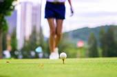 Golfball liegt auf hölzernem Abschlag und wartet auf Frau, die auf Abschlag im Golfplatz geht