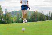 Fotografie Golferin in der Kontrolllinie, um den Ball auf das Fairway zu schlagen, zu Fuß, um den Golfball nach der Zielkontrolle der Linie zu treffen